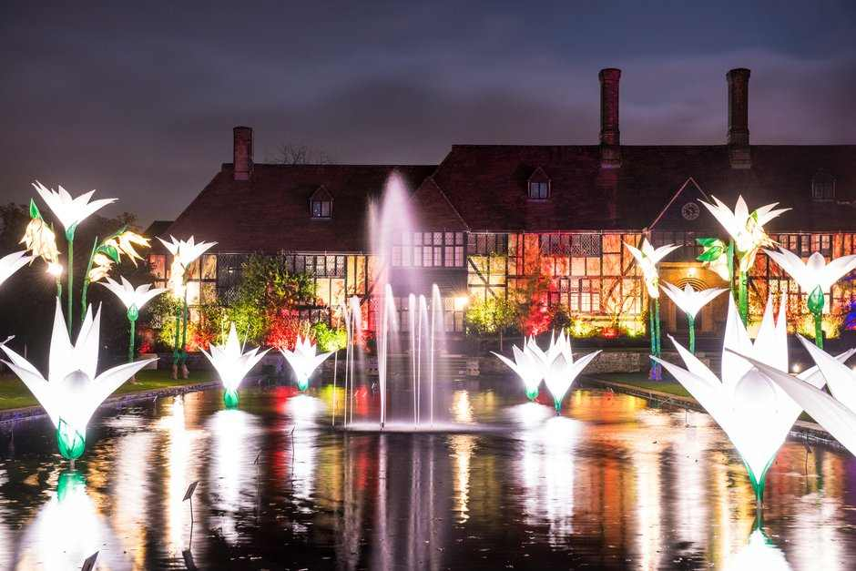 View of the Laboratory and floating flowers lights installations reflected in the Jellicoe Canal during the Christmas Glow 2017, RHS Garden Wisley